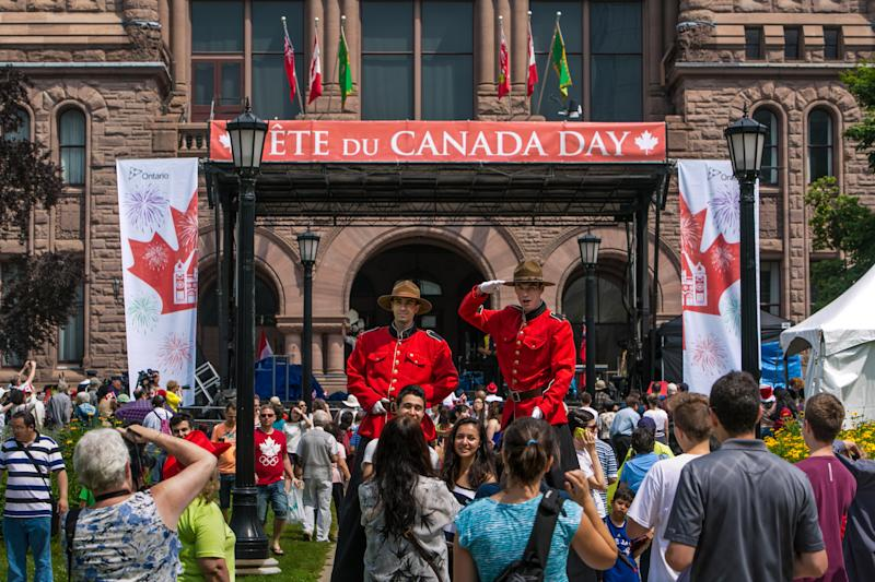 TORONTO, CANADA - JULY 1: A crowd gathers for the Canada Day celebration on the lawn of the Legislative Building at Queen's Park on July 1, 2014 in Toronto, Ontario, Canada. Canada's most populous city is undergoing a major economic boom with high-rise construction and renovation projects underway throughout the downtown and outlying neighborhoods. (Photo by George Rose/Getty Images)