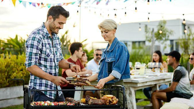 Happy man serving meat while woman holding board.
