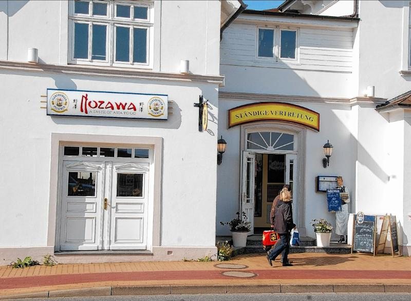 """FILE - In this May 13, 2013 file picture, persons pass the restaurant 'Nozawa', left,  in Westerland on the German North Sea island of Sylt. Authorities in Germany said Friday May 17, 2013 they are investigating a Japanese chef's death following a fight with two customers who had complained about his food.  Prosecutors say Miki Nozawa died Monday May 13, 2013  following a brawl with the two men at a nightclub near his restaurant on the North Sea resort island of Sylt.  German tabloid newspaper Bild reported the men had refused to pay for a dish of fried rice with vegetables and beef. The paper said Nozawa was a """"star chef"""" who previously worked in Berlin and Sardinia. (AP Photo/dpa,Friederike Reussner,file)"""