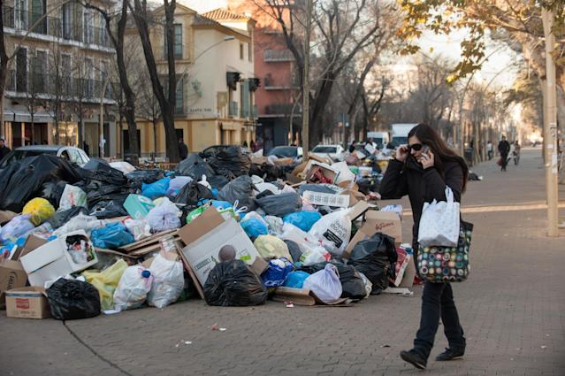 SEVILLE, SPAIN - FEBRUARY 05: A pedestrian passes a pile of garbage during the ninth day of the Seville waste disposal strike on February 5, 2013 in Seville, Spain. Workers are striking over demands they take a 5% pay cut and extend their working week to 37.5 hours. (Photo by Denis Doyle/Getty Images)