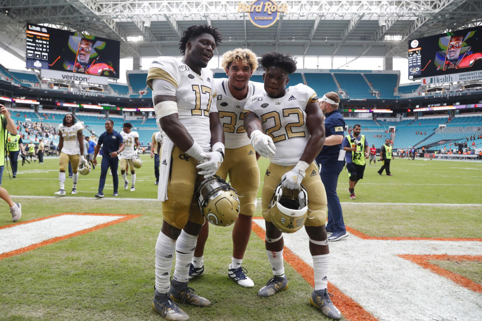 """FILE - Saturday, Oct. 19, 2019 file photo, Georgia Tech defensive lineman Sylvain Yondjouen of Belgium (32) poses with linebacker Demetrius Knight II (17) and running back Jamious Griffin (22) after an NCAA college football game against Miami, in Miami Gardens, Fla. Football in Europe usually means """"soccer."""" But increasingly European kids are excelling at American football. So much so that Europe has become a pipeline of recruits for college football programs — and increasingly for schools from the Power Five conferences. (AP Photo/Wilfredo Lee, file)"""