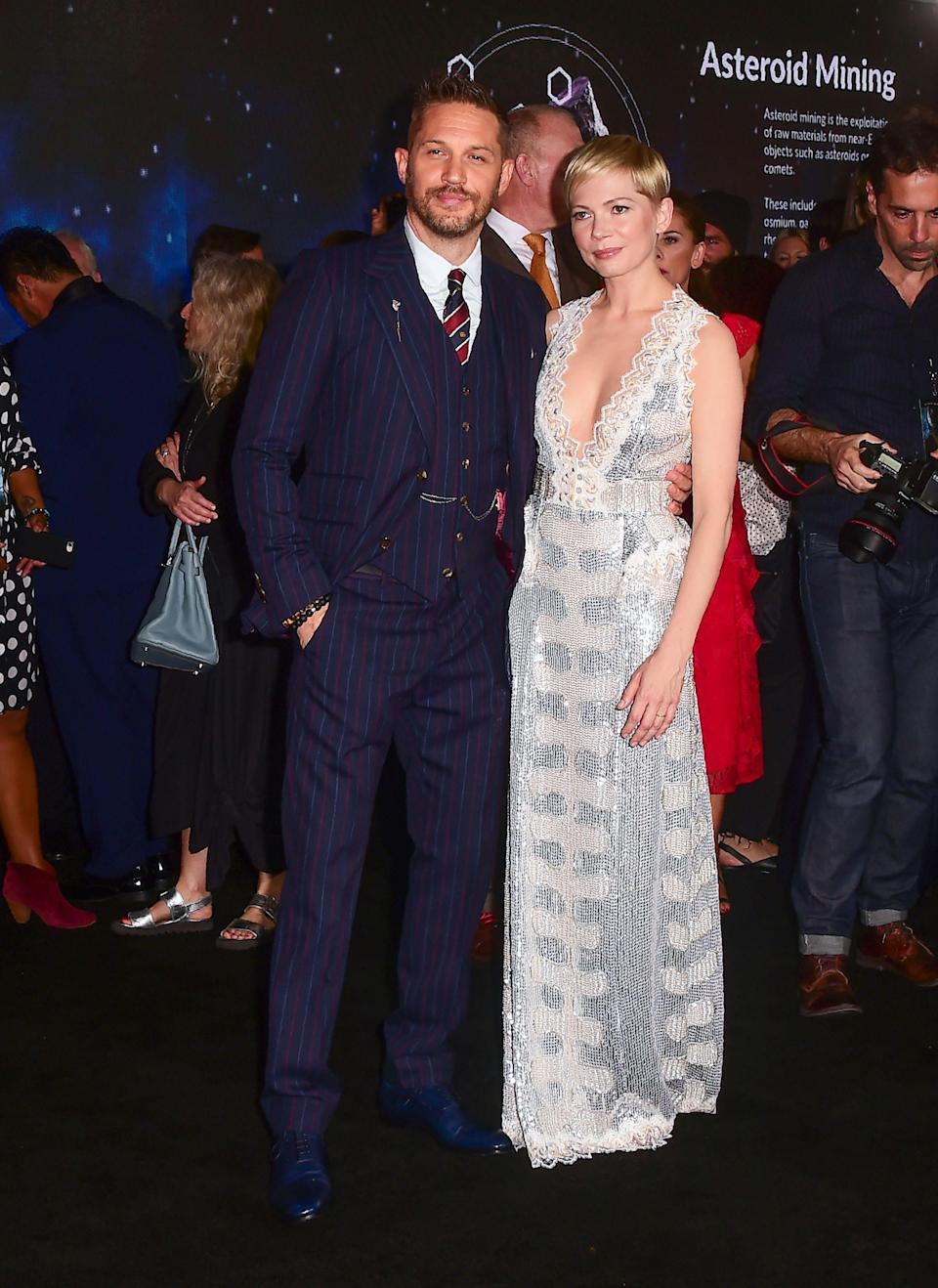 <p>Michelle Wiliams and Tom Hardy proved they scrub up well for the premiere of new film 'Venom'. Williams shimmered in a Louis Vuitton dress while Hardy dressed in a pinstripe suit. <em>[Photo: Getty]</em> </p>