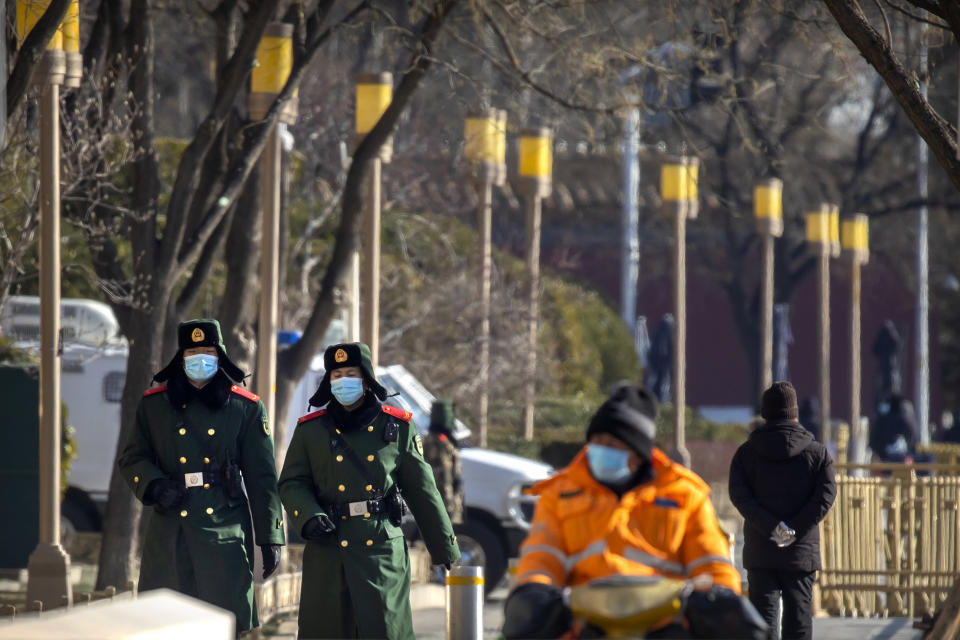 Chinese paramilitary police wearing face masks to protect against the spread of the coronavirus patrol along a street in Beijing, Saturday, Jan. 9, 2021. COVID vaccine shots will be free in China, where more than 9 million doses have been give to date, health officials in Beijing said Saturday. (AP Photo/Mark Schiefelbein)