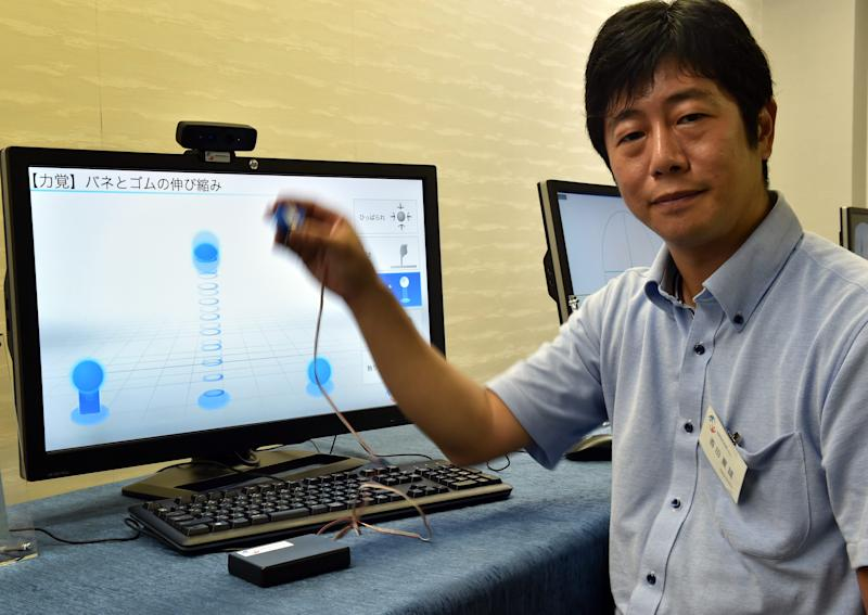 "Japan's high-tech venture Miraisens CEO Natsuo Koda demonstrates ""3D-Haptics Technology"" at a press preview in Tsukuba, suburban Tokyo, on September 1, 2014 (AFP Photo/Yoshikazu Tsuno)"