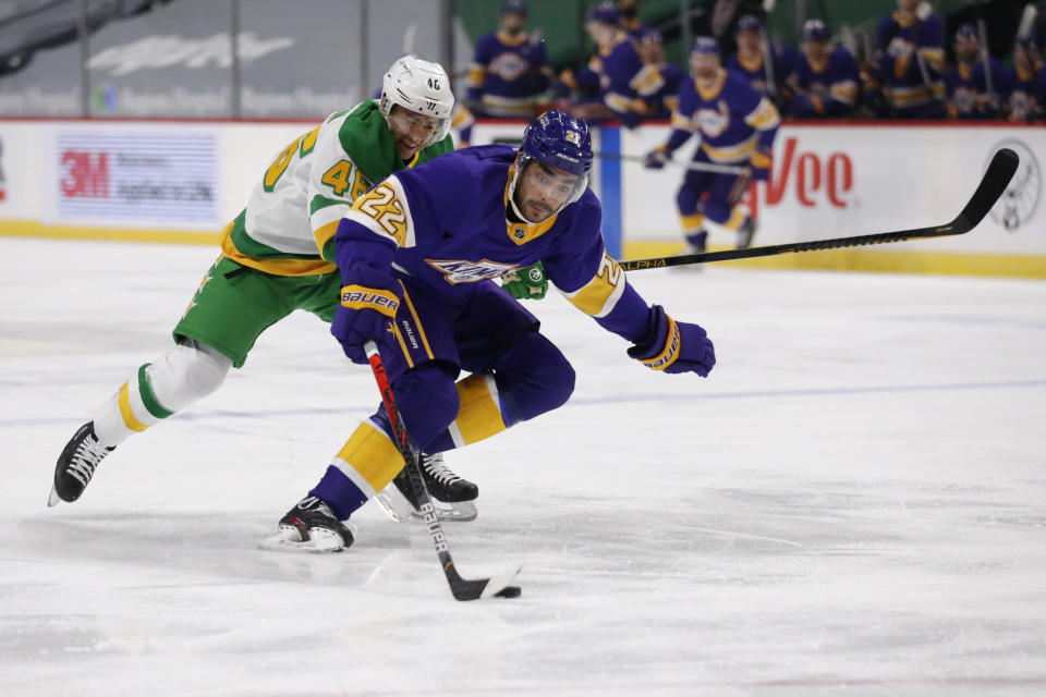 Los Angeles Kings left wing Andreas Athanasiou (22) controls the puck in front of Minnesota Wild defenseman Jared Spurgeon (46) in the first period during an NHL hockey game, Saturday, Feb. 27, 2021, in St. Paul, Minn. (AP Photo/Andy Clayton-King)