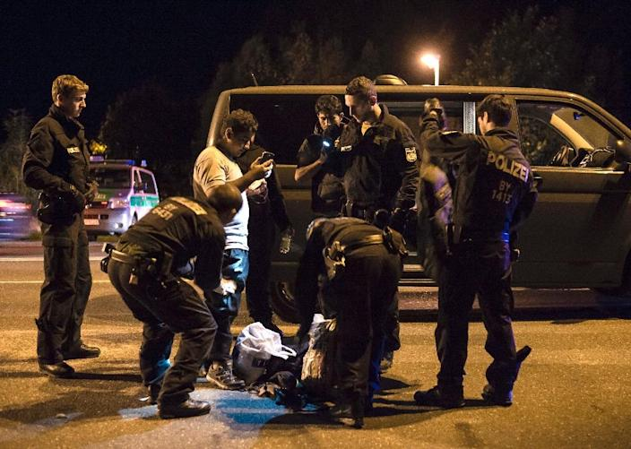 Policemen check migrants on September 13, 2015, in Freilassing at the border between Germany and Austria, after Berlin's shock decision to reintroduce such controls to halt a surge in refugee numbers (AFP Photo/Guenter Schiffmann)