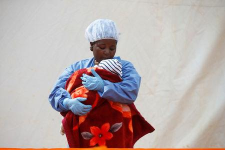 Rachel Kahindo, an Ebola survivor working as a caregiver to babies who are confirmed Ebola cases, holds an infant outside the red zone at the Ebola treatment centre in Butembo, Democratic Republic of Congo, March 25, 2019.  REUTERS/Baz Ratner
