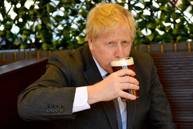 Prime Minister Boris Johnson enjoys a pint in the beer garden during a visit to The Mount pub and restaurant in Wolverhampton