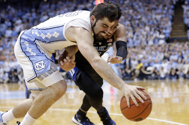 North Carolina's Luke Maye, left, and Duke's Tre Jones battle for the ball during the first half of an NCAA college basketball game in Chapel Hill, N.C., Saturday, March 9, 2019. (AP Photo/Gerry Broome)