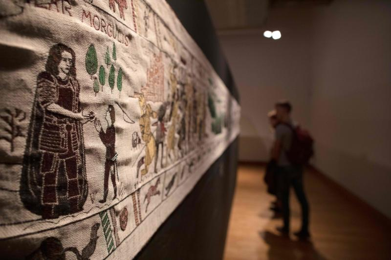 Members of the public look at completed sections of a tapestry depicting the hit television series Game of Thrones at the Ulster Museum in Belfast on July 5, 2019. - Like the Bayeux Tapestry, the Game of Thrones Tapestry is woven of fine linen and hand-embroidered, with decorative borders and a central pictorial narrative. It will reach 90m by the end of the final season of the show. (Photo by Paul Faith / AFP) (Photo credit should read PAUL FAITH/AFP/Getty Images)