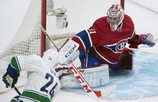 Montreal Canadiens goaltender Carey Price makes a save against Vancouver Canucks' Raphael Diaz during the second period of an NHL hockey game Thursday, Feb. 6, 2014, in Montreal. (AP Photo/The Canadian Press, Graham Hughes)