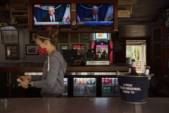 Tasia Markantonis, the manager of West Alabama Ice House in Houston, closes the tab of a customer on Friday, June 26, 2020, as a television displays news coverage of Vice President Mike Pence speaking during a coronavirus task force briefing. (Callaghan O'Hare/The New York Times)