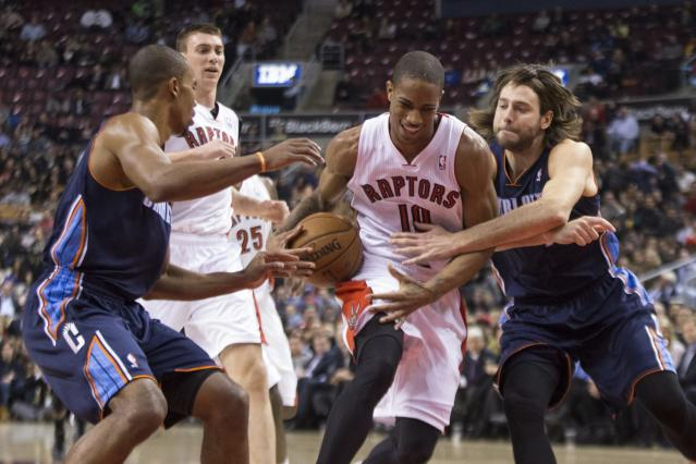 Toronto Raptors' DeMar DeRozan drives between Charlotte Bobcats' Josh McRoberts, right, and Ramon Sessions during the first half of an NBA basketball game in Toronto on Wednesday, Dec. 18, 2013. (AP Photo/The Canadian Press, Chris Young)