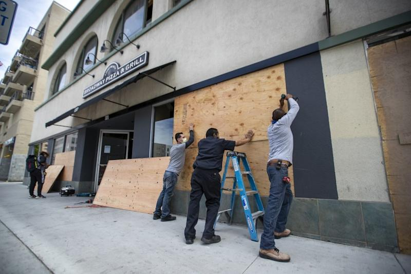LONG BEACH, CA - JUNE 01: After rioters looted, destroyed and burned businesses along Pine Ave. Sunday evening, a worker puts up sheets of plywood over windows of a business while California National Guard members patrol the streets Monday, June 1, 2020 in Long Beach, CA. (Allen J. Schaben / Los Angeles Times)