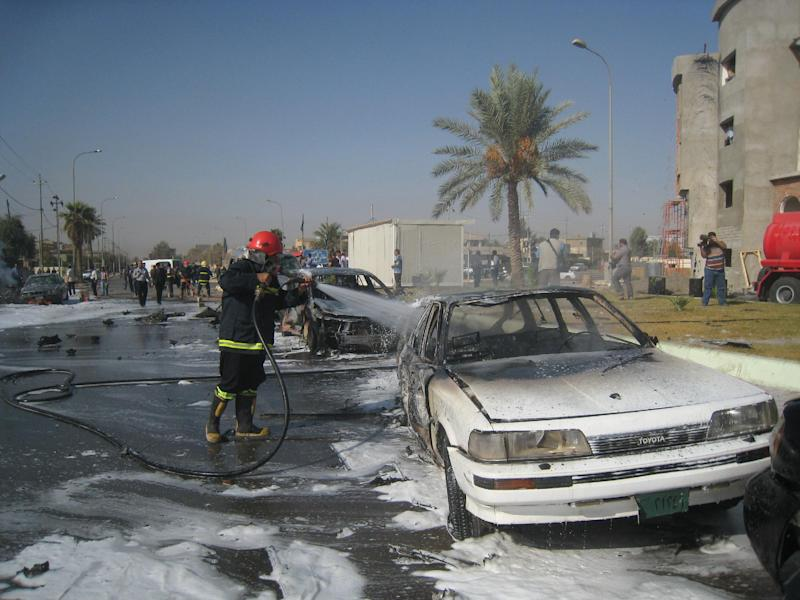 An Iraqi firefighter hoses down burned cars after a car bomb attack in Kirkuk, 180 miles (290 kilometers) north of Baghdad, Iraq, Monday, Oct. 15, 2012. Three people including two soldiers died and 22 others were wounded Monday in three attacks two car bombings and a shooting at a checkpoint in and around the city of Kirkuk, home to a combustible mix of Kurds, Sunni Arabs and Turkomen who all claim rights to the city. (AP Photo/Emad Matti)