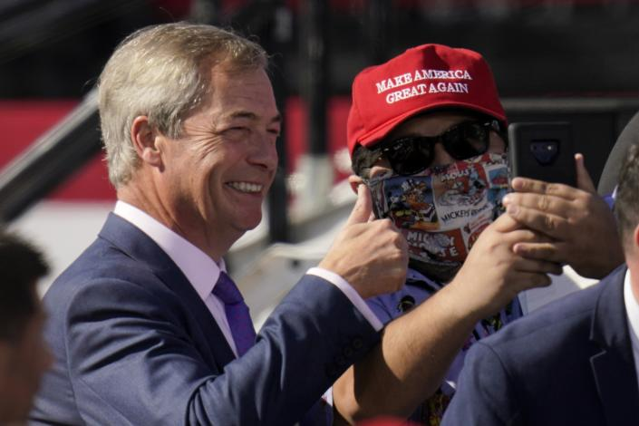 Nigel Farage, left, a former member of the European Parliament representing the UK and member of the Brexit Party, poses for a picture with a supporter of President Donald Trump prior to Trump arriving for a campaign rally at Phoenix Goodyear Airport Wednesday, Oct. 28, 2020, in Goodyear, Ariz. (AP Photo/Ross D. Franklin)