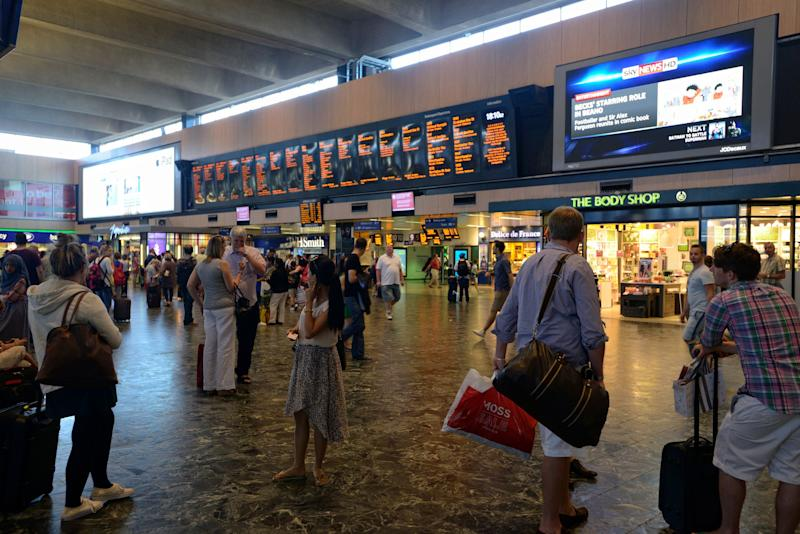 London, United Kingdom - July 21, 2013: Euston Train Station in London, with a man checking the timetable for his next train departure, with other commuters waiting in front of massive electronic departures/arrivals information board, while other travellers pass by to either other bus/train services or The Tube. Under the panel many fast foods, cafes and small retail shops and ATMs are available.Euston station is one of the busiest stations in London, along with St. Pancreas, Victoria and Waterloo stations, as it host the train, bus and underground services in one place.