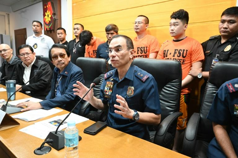 "Philippines Police Major General Guillermo Eleazar (2nd R) gestures during a press conference with other officials and three (back, orange shirts) of 277 Chinese arrested for ""illegal online operations"""