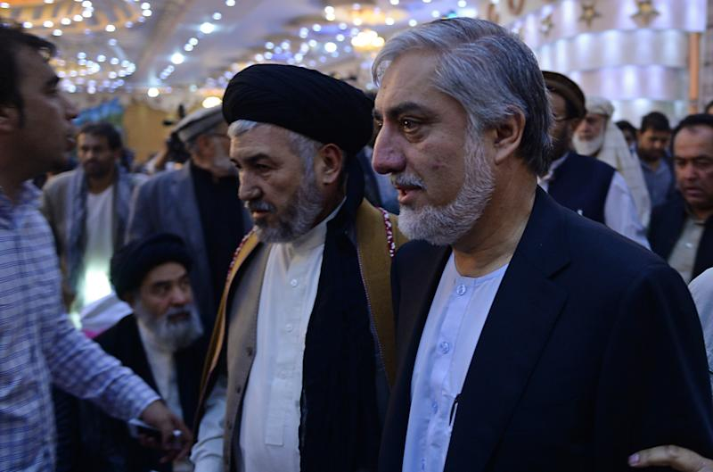Afghan presidential candidate Abdullah Abdullah (R) arrives for a gathering in Kabul on August 21, 2014