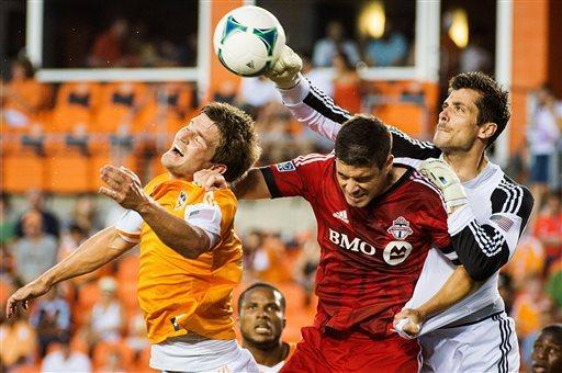 Houston Dynamo goalkeeper Tally Hall, right, punches the ball away from Toronto FC defender Darren O'Dea, second from right, and defender Bobby Boswell, left, during the first half of a a Major League Soccer game on Saturday, June 22, 2013, at BBVA Compass Stadium in Houston. (AP Photo/Houston Chronicle, Smiley N. Pool)
