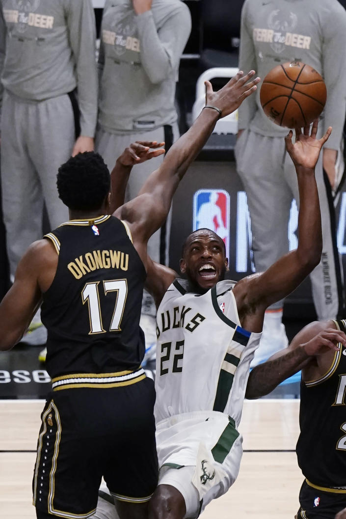 Milwaukee Bucks forward Khris Middleton (22) is fouled by Atlanta Hawks forward Onyeka Okongwu (17) during the second half of Game 6 of the Eastern Conference finals in the NBA basketball playoffs Saturday, July 3, 2021, in Atlanta. (AP Photo/John Bazemore)