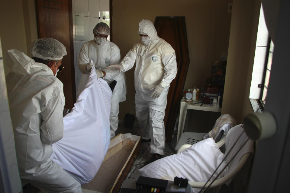 Public funeral service workers help to remove the body of Jose Bernardino Ferreira, 77, who died from complications related to COVID-19 in his home, in Manaus, Amazonas state, Friday, Jan. 22, 2021. The number of people who die in their homes amid the new coronavirus pandemic is growing due to the lack of availability in hospitals and the shortage of oxygen. (AP Photo/Edmar Barros)