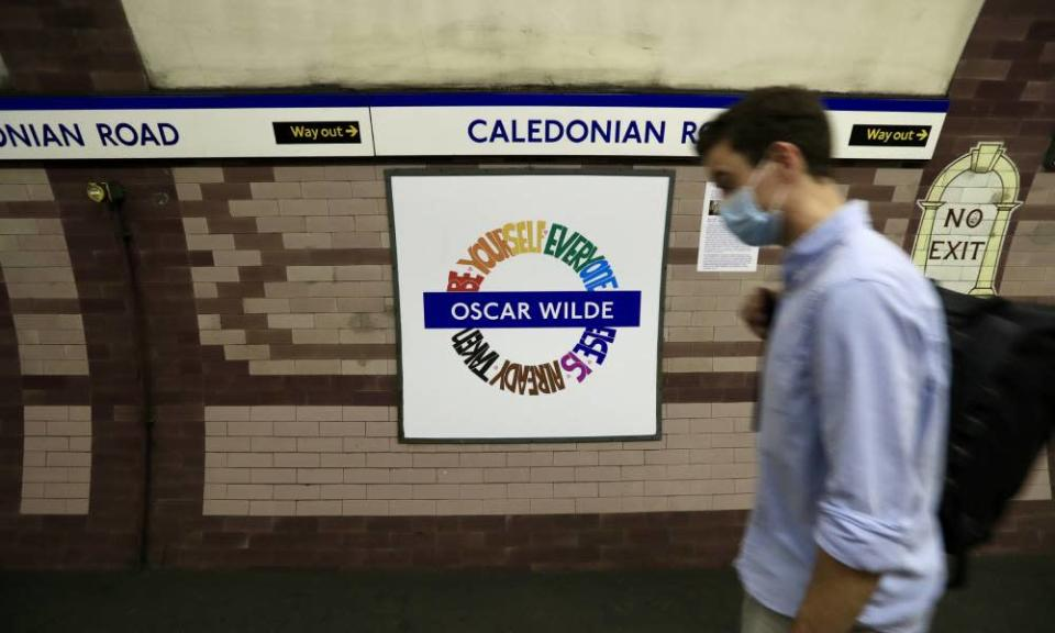 A person walks by the LGBT+ Pride London Underground roundel designed by Amy Lamé at the Caledonian Road station