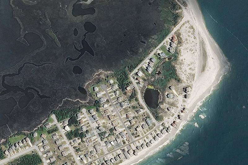 This earlier image shows sandy dunes stretching out much further (National Oceanic and Atmospheric Administration)