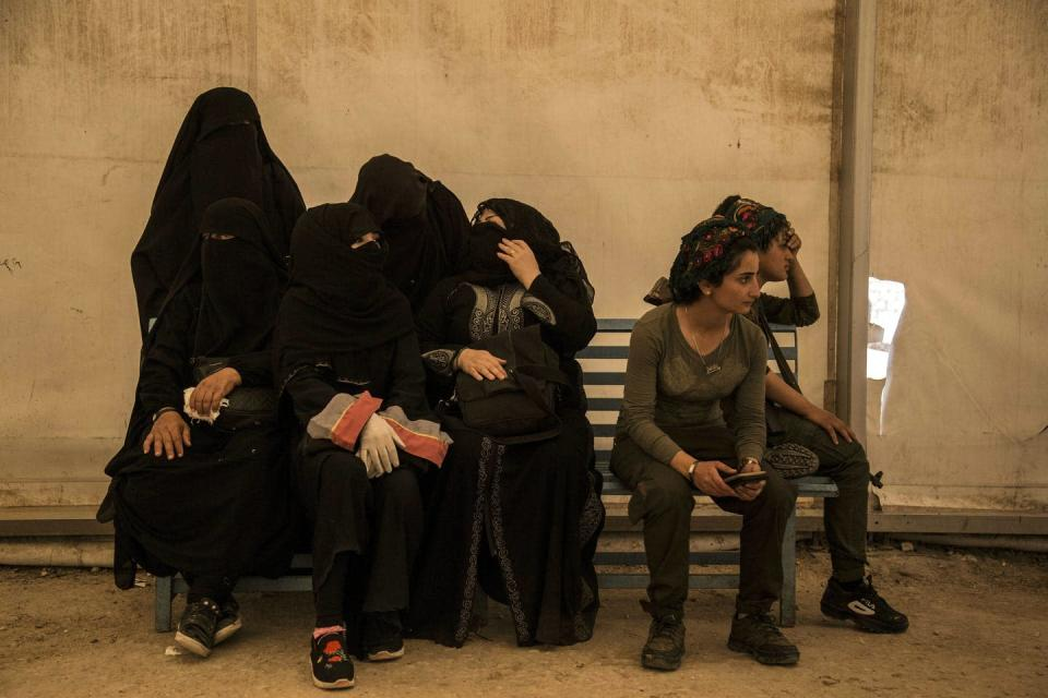 Women wearing niqabs sit huddled together on a bench