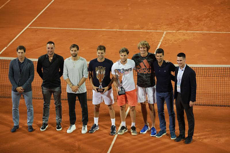 Dominic Thiem (4th R) and runner-up Filip Krajinovic (4th L) pose with their trophies after the final match along with Dusan Lajovic, Viktor Troicki, Grigor Dimitov, Alexander Zverev, Novak Djokovic and Djordje Djokovic at the Adria Tour charity exhibition.