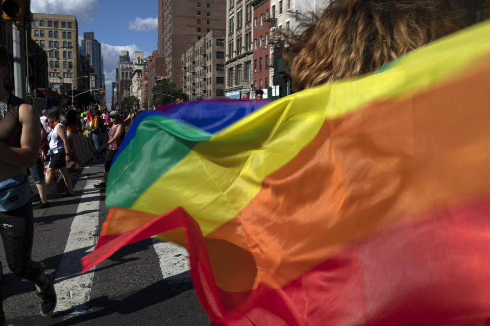 FILE - In this June 30, 2019, file photo parade-goers carrying rainbow flags walk down a street during the LBGTQ Pride march in New York, to celebrate five decades of LGBTQ pride, marking the 50th anniversary of the police raid that sparked the modern-day gay rights movement. Legislation that would create new protections for LGBTQ Americans is stalling out in the U.S. Senate. Democrats were hopeful they could pass the Equality Act this year since they control Congress and the White House. (AP Photo/Wong Maye-E, File)