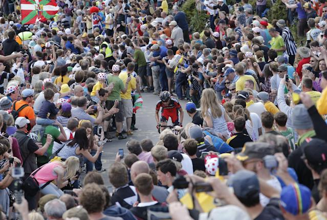 Spectators watch as a distanced rider climbs Bradfield Pass during the second stage of the Tour de France cycling race over 201 kilometers (124.9 miles) with start in York and finish in Sheffield, England, Sunday, July 6, 2014. (AP Photo/Christophe Ena)