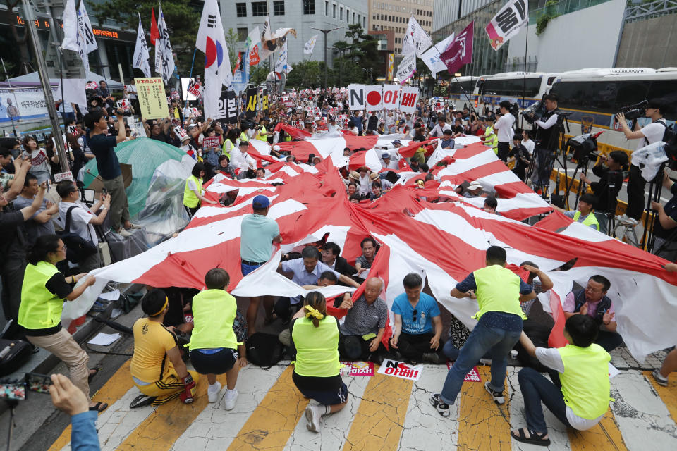 """FILE - In this July 20, 2019, file photo, protesters tear a Japanese rising sun flag during a rally denouncing the Japanese government's decision on their exports to South Korea in front of Japanese Embassy in Seoul, South Korea. Japan's """"rising sun"""" flag is raising anger at the Olympics, with some of the host nation's neighbors calling for it to be banned during the Tokyo Games, which start Friday, July 23, 2021. (AP Photo/Ahn Young-joon, File)"""