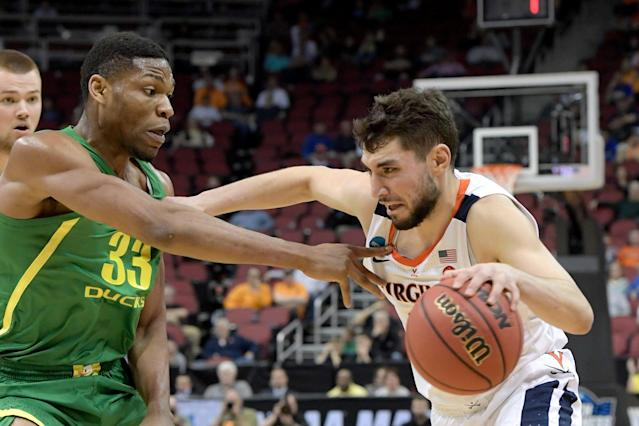 Virginia's Ty Jerome, right, drives against Oregon's Francis Okoro (33) during the second half of a men's NCAA Tournament college basketball South Regional semifinal game, Thursday, March 28, 2019, in Louisville, Ky. (AP Photo/Timothy D. Easley)