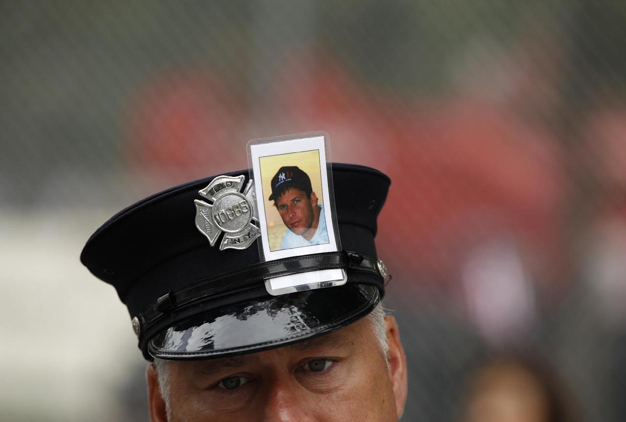 A New York City firefighter wears photo in his hatband of a victim of the Sept. 11, 2001 World Trade Center attacks during 10th anniversary ceremonies at the National September 11 Memorial , in New York, Sunday, Sept. 11, 2011. (AP Photo/Lucas Jackson)