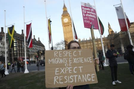 FILE PHOTO - A demonstrator holds a placard during a protest in favour of amendments to the Brexit Bill outside the Houses of Parliament, in London