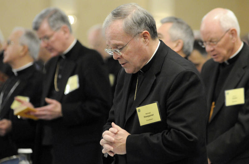 FILE - In this Nov. 10, 2008, Bishop Michael Hoeppner, center, of Crookston, Minn., prays during a semi-annual meeting of the United States Conference of Catholic Bishops in Baltimore. The Roman Catholic archbishop of St. Paul and Minneapolis says he has opened an investigation under a new Vatican protocol into allegations that the bishop of Crookston interfered with investigations into clerical sexual misconduct. Archbishop Bernard Hebda made the announcement Wednesday Sept. 11, 2019. His statement says the investigation targets Bishop Michael Hoeppner of the Crookston diocese in northwestern Minnesota. (AP Photo/ Steve Ruark,File)