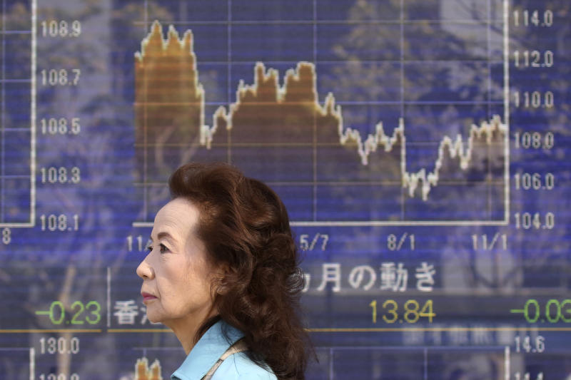 In this Thursday, Nov. 21, 2019, photo, a woman walks by an electronic stock board of a securities firm in Tokyo. Stocks logged modest gains Friday, Nov. 22, 2019, in Asia after a lackluster overnight session on Wall Street ended with the market's third straight drop. (AP Photo/Koji Sasahara)