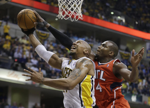 Indiana Pacers' David West (21) has his shot blocked by Atlanta Hawks' Paul Millsap (4) during the second half in Game 5 of an opening-round NBA basketball playoff series Monday, April 28, 2014, in Indianapolis. Atlanta defeated Indiana 107-97. (AP Photo/Darron Cummings)