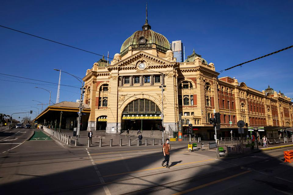 People are seen crossing a quiet Flinders Street in Melbourne, Australia. Source: Getty Images
