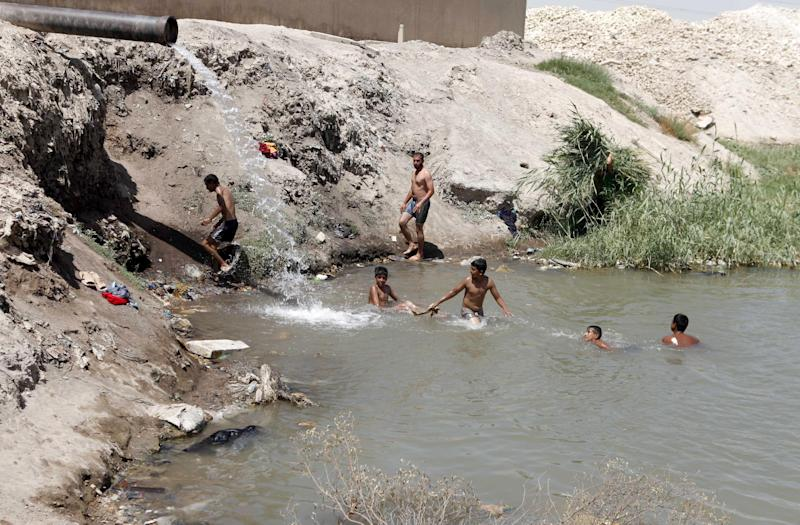 In this Thursday, Aug. 16, 2012 photo, Iraqi children cool off by swimming in a garbage-filled pond fed by wastewater runoff in Baghdad, Iraq. Iraq is fast becoming an oil producing powerhouse, but many Iraqis see little reason to celebrate the postwar petroleum gains that have turned Iraq into a leading oil producer. (AP Photo/Karim Kadim)
