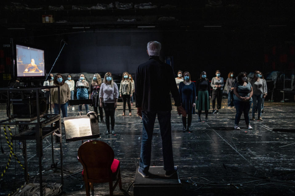 "Andres Maspero directs the chorus backstage during a performance of ""Rusalka"" at the Teatro Real in Madrid, Spain, on Thursday, Nov. 12, 2020. The theater is one of the few major opera houses that have reopened during the coronavirus pandemic, although to smaller audiences. (AP Photo/Bernat Armangue)"