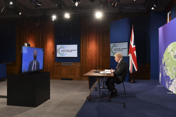 FILE - In this April 22, 2021 file photo, British Prime Minister Boris Johnson listens to U.S. President Joe Biden, on screen, during the opening session of the virtual global Leaders Summit on Climate, as he sits in the Downing Street Briefing Room in central London. On Biden's first foreign trip as president, he will find many of his hosts in Europe welcoming but wary after a tense four years between Europe and the U.S. under former President Donald Trump. (Justin Tallis/Pool Photo via AP, File)