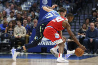 Dallas Mavericks forward Luka Doncic (77) and Sacramento Kings forward Harrison Barnes (40) chase a loose ball in the first half of an NBA basketball game Sunday, Dec. 8, 2019, in Dallas. (AP Photo/Richard W. Rodriguez)