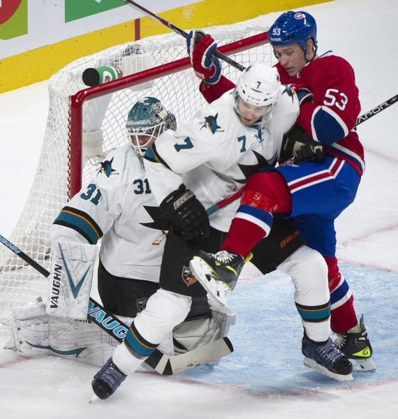 Montreal Canadiens' Ryan White, right, pressures San Jose Sharks' Brad Stuart (7) as Sharks goaltender Antti Niemi defends his net during the first period of an NHL hockey game in Montreal, Saturday, Oct. 26, 2013. (AP Photo/The Canadian Press, Graham Hughes)