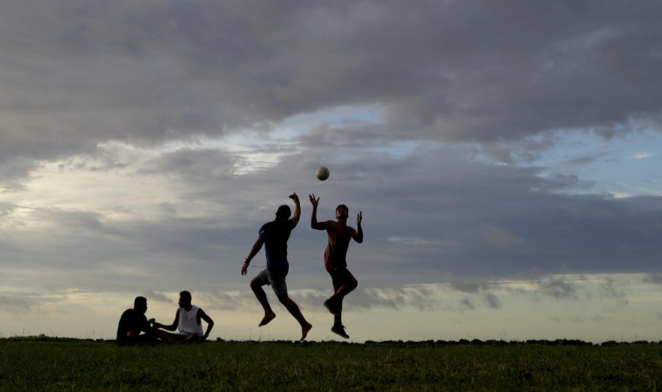 In this Wednesday, April 10, 2019, photo, young men play a game of rugby at sunset in Nuku'alofa, Tonga. China is pouring billions of dollars in aid and low-interest loans into the South Pacific, and even in the far-flung kingdom of Tonga there are signs that a battle for power and influence among much larger nations is heating up and could exact a toll. (AP Photo/Mark Baker)