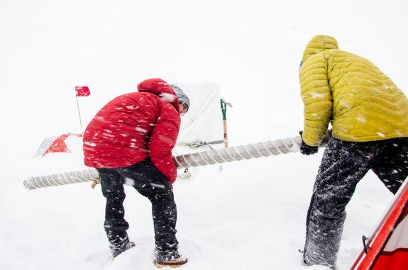 Scientists removing an ice core drill amid inclement weather.