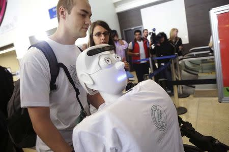 Alexander Herzog, a doctoral student at Max Planck Society, pushes 'Athena', the first 'humanoid' robot to fly as a passenger, as  they arrive at Los Angeles International Airport, California December 15, 2014. REUTERS/Jonathan Alcorn