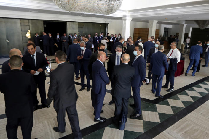 Lebanese lawmakers and ministers wait in the foyer due to a power outage for a meeting to confirm Lebanon's new government, at a theater known as the UNESCO palace so that parliament members could observe social distancing measures imposed over the coronavirus pandemic, in Beirut, Lebanon, Monday, Sept. 20, 2021. Electricity later came back 40 minutes later and the meeting was held. (AP Photo/Bilal Hussein)
