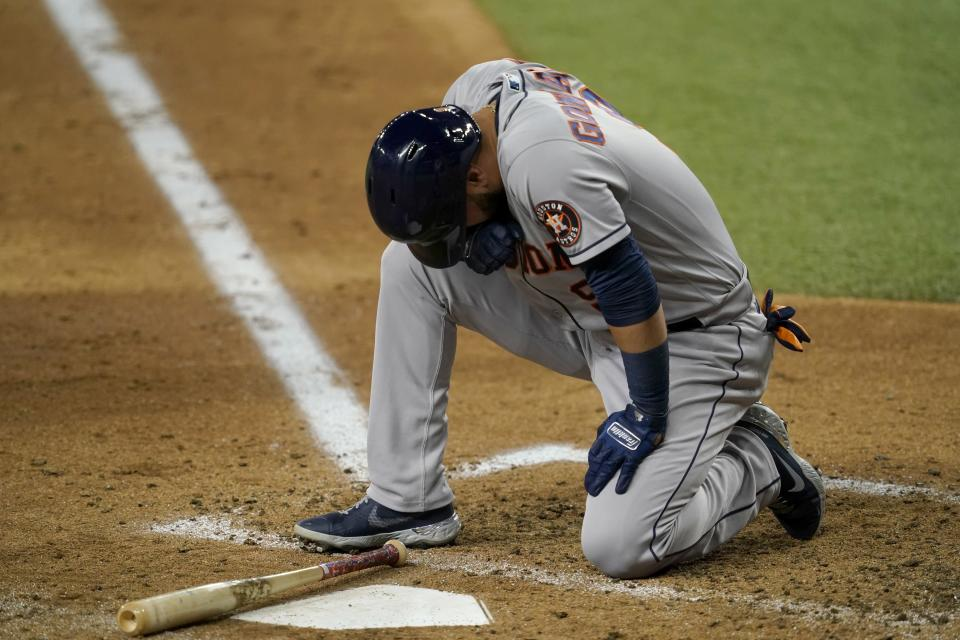 Houston Astros' Marwin Gonzalez kneels by the plate after being hit in the bottom right leg by a pitch thrown by Texas Rangers starter Kohei Arihara in the fourth inning of a baseball game in Arlington, Texas, Wednesday, Sept. 15, 2021. Gonzalez remained in the game. (AP Photo/Tony Gutierrez)